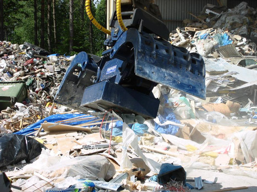 demolition grapple with scrap magnet cleaning up a waste site