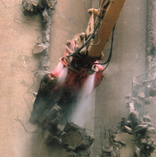 Dynaset Dust Suppression System spraying towards a grapple at a demolition site