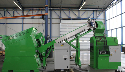 Green wire shredder machine feeding scrap wire to a green wire recycling system