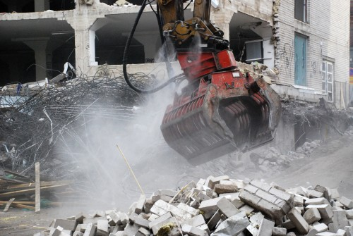 Dynaset Dust Suppression System spraying from a grapple at a demolition site