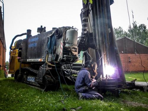 Man welding a drilling machine with a welder generator and welder stick