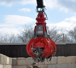 red scrap grapple with magnet moving scrap metal