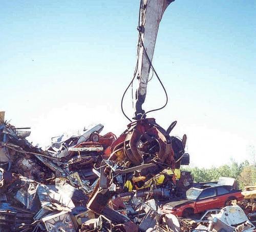 red hydraulic five tine grapple moving scrap metal