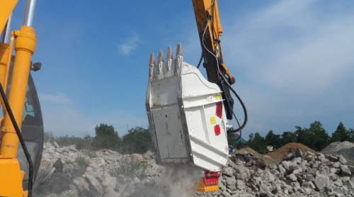 crusher bucket crushing rock at demolition site