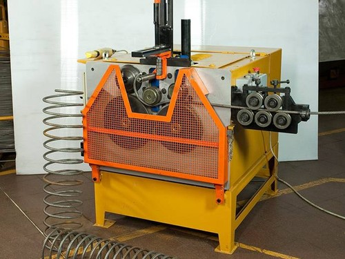 Yellow and orange machine with rebar passing through it for rebar hoop bending